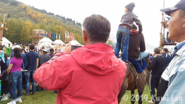 馬の背に乗って観戦するお子さん